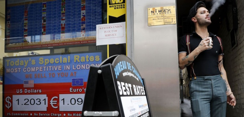 A man stands and smokes a cigarette alongside a board diplaying the price of Euro and US dollars against British pound Sterling, outside a currency exchange store in central London on October 13, 2016. Dutch food giant Unilever, reportedly caught up in a pricing war with a British supermarket chain, warned Thursday the falling pound will likely hike its prices in Britain. The British pound has faced turbulence recently, last week plummeting against the dollar to its lowest level for 31 years, amid uncertainty over the impact of the country's planned Brexit from the European Union. / AFP / Adrian DENNIS        (Photo credit should read ADRIAN DENNIS/AFP/Getty Images)