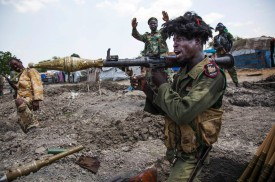 """TOPSHOT - soldiers of the Sudan People Liberation Army (SPLA) celebrate while standing in trenches in Lelo, outside Malakal, northern South Sudan, on October 16, 2016.   Heavy fighting broke out on Ocotober 14 between SPLA (Government) and opposition forces in Wajwok and Lalo villages, outside Malakal. SPLA commanders claim they succeeded to keep their positions and assure their forces just responded """"on self defence"""". / AFP / Albert Gonzalez Farran        (Photo credit should read ALBERT GONZALEZ FARRAN/AFP/Getty Images)"""