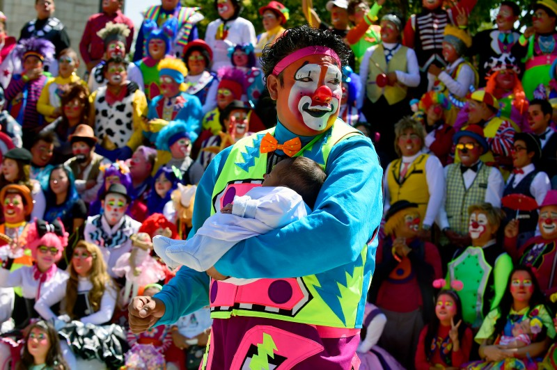 "A Clown holds a baby during the family photo shooting at the XXI Convention of Clowns, at the Jimenez Rueda Theatre, in Mexico City on October 19, 2016. Latin American clowns hold their 21st annual conference in Mexico City from October 17 through 20. The lurking clown phenomenon as a wave of hysteria about sightings of ""creepy"" or ""killer"" clowns that sweeps the United States and European nations concern those present. / AFP / Alfredo ESTRELLA        (Photo credit should read ALFREDO ESTRELLA/AFP/Getty Images)"
