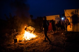 CALAIS, FRANCE - OCTOBER 24: A migrant throws a wooden crate on to a bonfire at the Jungle migrant camp on October 24, 2016 in Calais, France. French authorities have begun to clear the estimated 7000 people from the Calais Jungle migrant and refugee camp ahead of its demolition. (Photo by Jack Taylor/Getty Images)