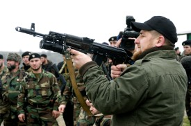 """TSENTEROI, CHECHNYA, RUSSIA - NOVEMBER 2005:  Ramzan Kadyrov proudly displays his shooting skills at a firing range in his village of Tsentoroi in front of members of his private army. Officially his army are known as the anti-terrorism squad, but everyone refers to its soldiers as Kadyrovtsy - """"Kadyrov's guys"""". Ramzan was born 5 October 1976 in Tsenteroi, Chechnya, and was made Prime Minister of Chechnya in the beginning of March 2006 and leader of a powerful Chechen militia known as kadyrovtsy. He is the son of former Chechen President Akhmad Kadyrov, who was assassinated in May 2004. He has the backing of Russian President Vladimir Putin, and was awarded the Hero of Russia medal, the highest honorary title of the Russian Federation. As the head of the Chechen Presidential Security Service, Kadyrov has often been accused of being brutal, ruthless and antidemocratic; according to media and human rights groups, he was personally implicated in several instances of torture and murder. It is also rumoured that he owns a private prison in his stronghold village of Tsenteroi, where he uses inmates as a punching bags. Kadyrov is known for keeping a pet lion cub, given to him as a gift after the birth of his first son, as well as a tiger and a number of a fighting dogs, and also used to own a wolf and a bear. He has only a few classes of elementary education finished; despite his lack of education, Kadyrov is a honorary member of the Russian Academy of Sciences.  (Photo by Kadyrov Press Office/Getty Images)"""