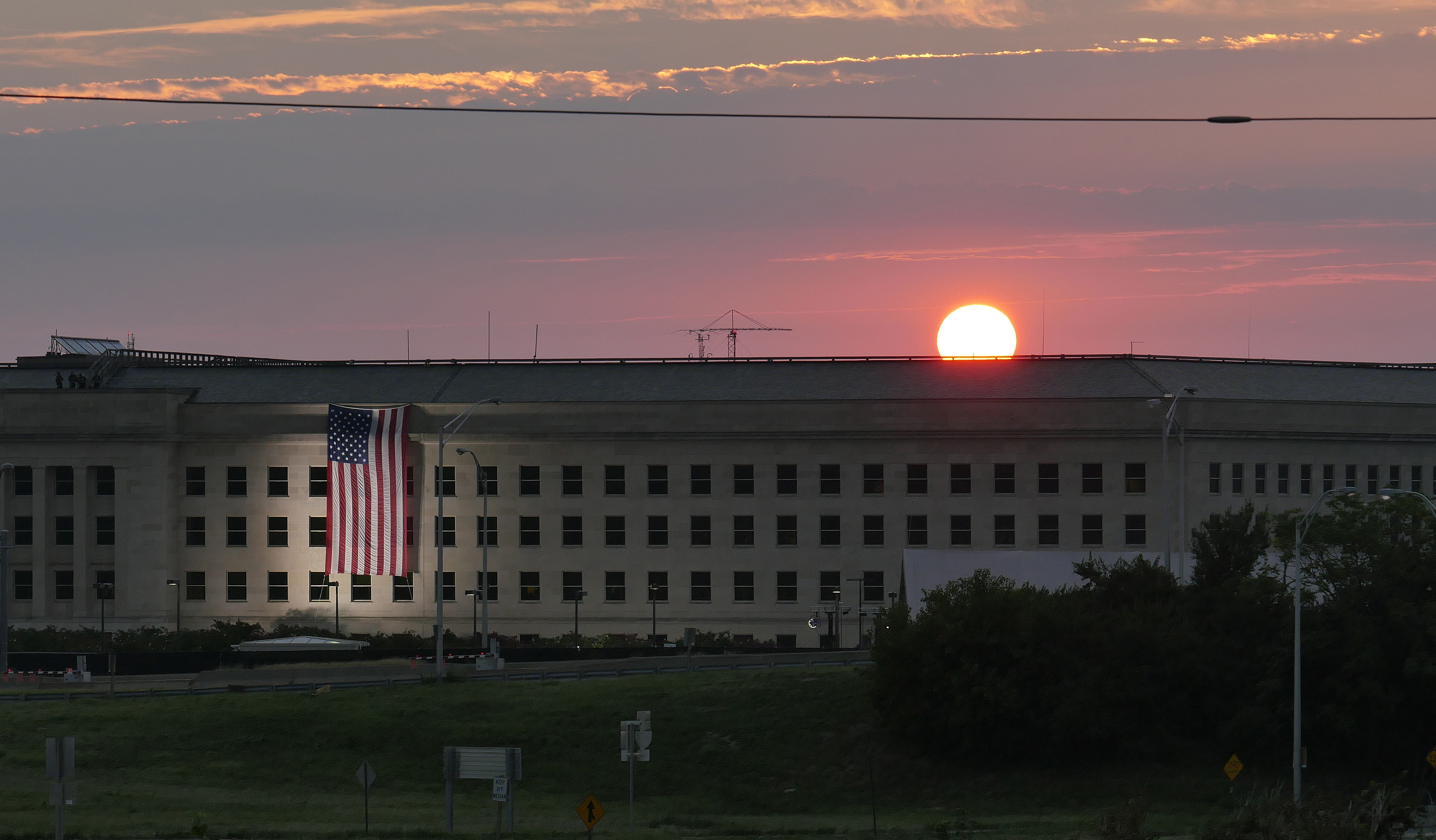 ARLINGTON, VA - SEPTEMBER 11: In this U.S. Navy handout, sunrise at the Pentagon prior to a ceremony to commemorate the 15th anniversary of the Sept. 11, 2001 terror attacks. The American flag is draped over the site of impact at the Pentagon. Photo by Damon J. Moritz