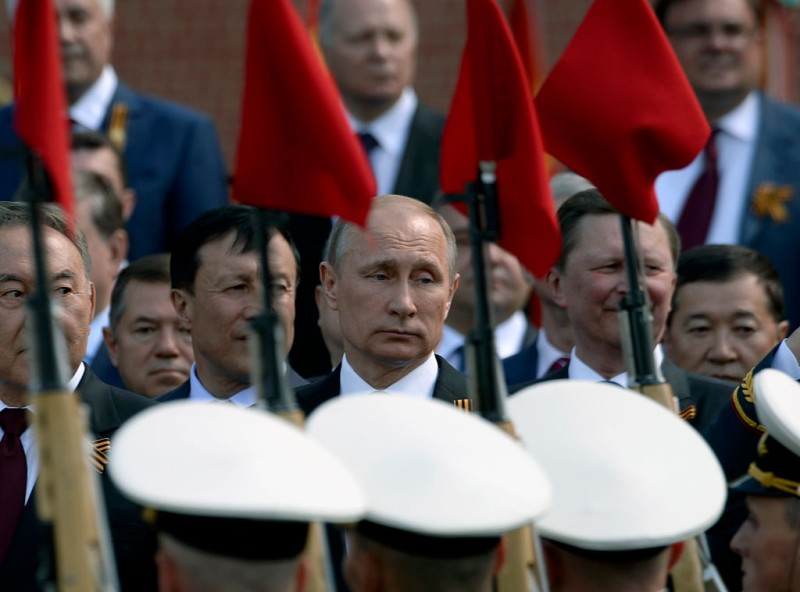 Russian President Vladimir Putin (C) takes part in a wreath laying ceremony at the Tomb of the Unknown Soldier by the Kremlin Wall in Moscow on May 9, 2016.  Russia marks the 71st anniversary of the Soviet Union's victory over Nazi Germany in World War II. / AFP / NATALIA KOLESNIKOVA        (Photo credit should read NATALIA KOLESNIKOVA/AFP/Getty Images)