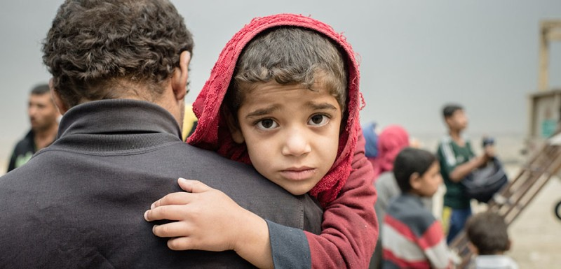 A man holds his son while waiting for board a military transport vehicle to a refugee camp on Oct. 25.