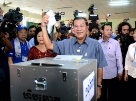 PHNOM PENH, CAMBODIA - JULY 28:  (CHINA OUT, SOUTH KOREA OUT) Cambodian Prime Minister Hun Sen (C) casts his vote with his wife Bun Rany (L) during the Cambodian general elections on July 28, 2013 in Phnom Penh, Cambodia. Cambodians go to the polls today in the fifth parliamentary election since 1993. 123 seats in the National Assembly are up for grabs to eight listed parties, with the main contenders being the ruling Cambodian Peoples Party (CPP) and the leading opposition Cambodia National Rescue Party (CNRP) led by Sam Rainsy.  (Photo by The Asahi Shimbun via Getty Images)