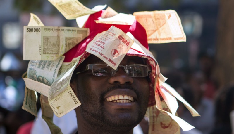 A man wearing a hat decorated with worthless note bearers' cheques during a protest against government plans to introduce bond notes -- a local token currency equivalent to the US dollar, and unemployement on August 3, 2016 in Harare.    Many Zimbabweans fear the bond notes could revive the hyperinflation that destroyed the economy in 2008 and 2009. Police squads had earlier closely monitored the marchers, who had planned to hand in a petition at the finance ministry to demand the bond notes are not issued. / AFP / ZINYANGE AUNTONY        (Photo credit should read ZINYANGE AUNTONY/AFP/Getty Images)