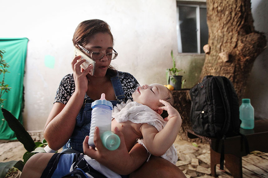RECIFE, BRAZIL - DECEMBER 13:  David Henrique Ferreira, who was born with microcephaly, is held by his mother Mylene as she speaks on the phone on December 13, 2016 in Recife, Brazil. As many of the babies born with microcephaly, believed to be linked to the Zika virus, turn one year old in Recife, doctors and mothers are adapting and learning treatments to assist and calm the children. Many suffer a plethora of difficulties including vision and hearing problems with doctors now labeling the overall condition as Ôcongenital Zika syndromeÕ. Authorities have recorded thousands of cases in Brazil in which the mosquito-borne Zika virus may have led to microcephaly in infants. Microcephaly results in an abnormally small head in newborns and is associated with various disorders. The state with the most cases is Pernambuco, whose capital is Recife.  (Photo by Mario Tama/Getty Images)