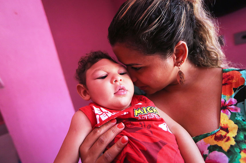 "RECIFE, BRAZIL - DECEMBER 12:  Juan Pedro, who has microcephaly and turned 1 year old on December 4, is held by his godmother Sinthia on December 12, 2016 in Recife, Brazil. As many of the babies with microcephaly, believed to be linked to the Zika virus, turn 1 year old in Recife, doctors and mothers are adapting and learning treatments to assist and calm the children. Many of the children are suffering a plethora of difficulties including vision and hearing problems with doctors now labeling the overall condition as ""congenital Zika syndrome."" Authorities have recorded thousands of cases in Brazil in which the mosquito-borne Zika virus may have led to microcephaly in infants. Microcephaly results in an abnormally small head in newborns and is associated with various disorders. The state with the most cases is Pernambuco, whose capital is Recife, and is being called the epicenter of the outbreak.  (Photo by Mario Tama/Getty Images)"