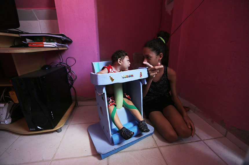 "RECIFE, BRAZIL - DECEMBER 12:  Juan Pedro, who has microcephaly and turned 1 year old on December 4, sits in a specially designed chair to keep him upright with his sister Jennifer Karine on December 12, 2016 in Recife, Brazil. As many of the babies with microcephaly, believed to be linked to the Zika virus, turn 1 year old in Recife, doctors and mothers are adapting and learning treatments to assist and calm the children. Many of the children are suffering a plethora of difficulties including vision and hearing problems with doctors now labeling the overall condition as ""congenital Zika syndrome."" Authorities have recorded thousands of cases in Brazil in which the mosquito-borne Zika virus may have led to microcephaly in infants. Microcephaly results in an abnormally small head in newborns and is associated with various disorders. The state with the most cases is Pernambuco, whose capital is Recife, and is being called the epicenter of the outbreak.  (Photo by Mario Tama/Getty Images)"