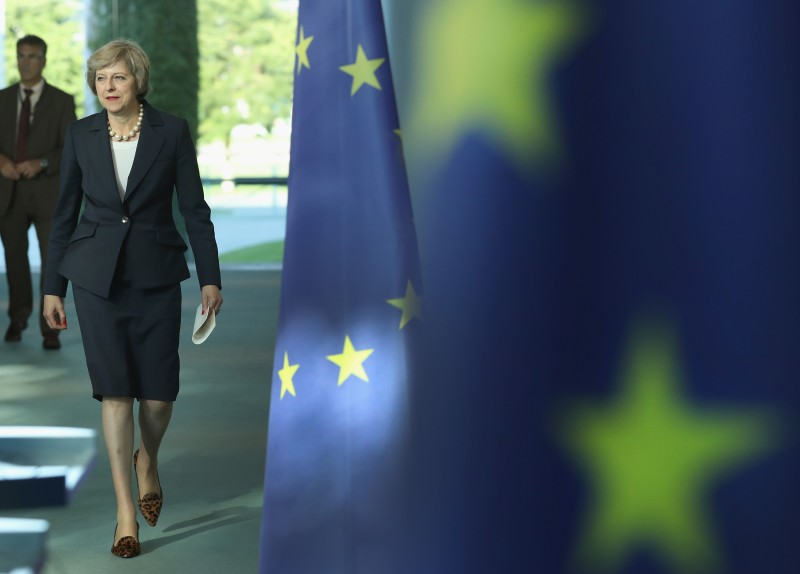 BERLIN, GERMANY - JULY 20:  British Prime Minister Theresa May walks past European Union flags as she and German Chancellor Angela Merkel (not pictured) arrive to speak to the media following talks at the Chancellery on July 20, 2016 in Berlin, Germany. May, who replaced David Cameron as prime minister last week in the wake of the Brexit vote that will take the United Kingdom out of the European Union, is visiting Germany and France in her first foreign trip since assuming office.  (Photo by Sean Gallup/Getty Images)