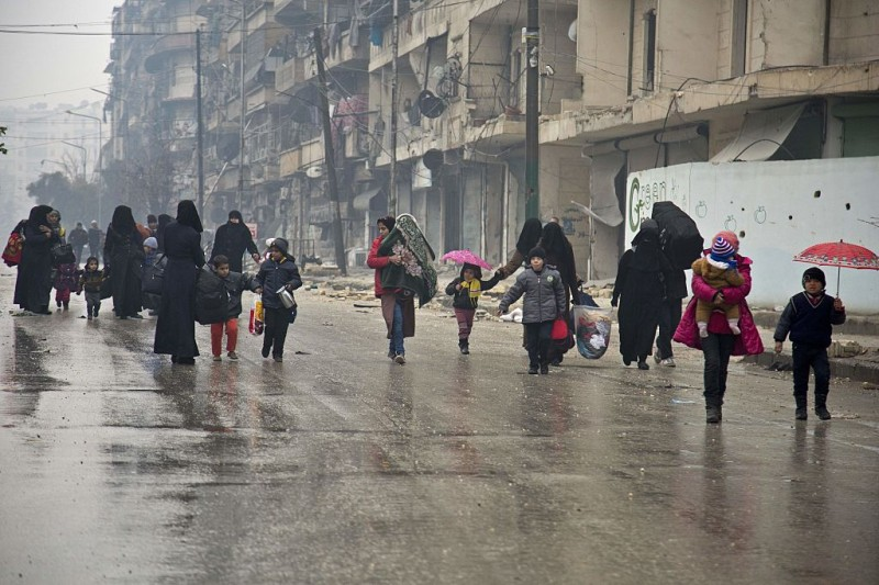 Syrians leave a rebel-held area of Aleppo towards the government-held side on December 13, 2016 during an operation by Syrian government forces to retake the embattled city. UN chief Ban Ki-moon expressed alarm over reports of atrocities against civilians Monday, as the battle for Aleppo entered its final phase with Syrian government forces on the verge of retaking rebel-held areas of the city.   / AFP / KARAM AL-MASRI        (Photo credit should read KARAM AL-MASRI/AFP/Getty Images)