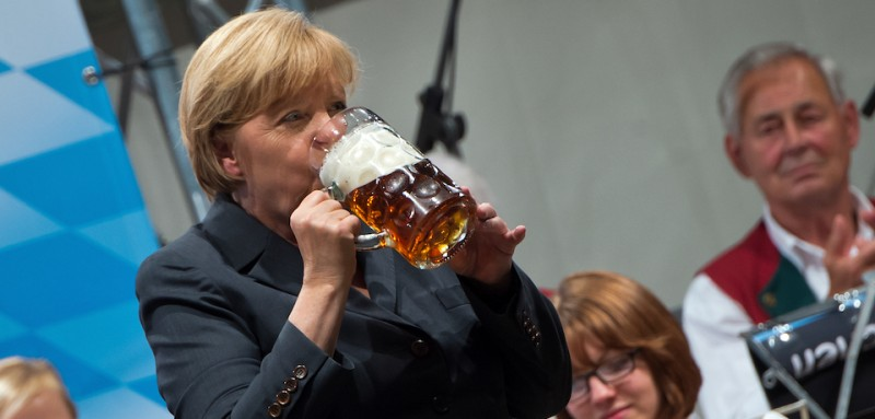 DACHAU, GERMANY - AUGUST 20:  German Chancellor and Chairwoman of the German Christian Democrats (CDU) Angela Merkel drinks a beer after speaking at an election campaign stop in a fest tent on August 20, 2013 in Dachau, Germany. Merkel has a strong lead over her political rivals and the CDU is expected to win federal elections scheduled for September 22, though what kind of governing coalition the CDU will be able to form remains uncertain.  (Photo by Joerg Koch/Getty Images)
