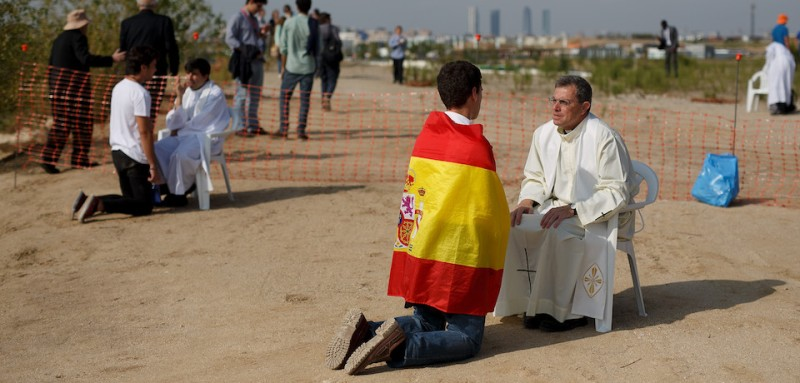 MADRID, SPAIN - SEPTEMBER 27:  A priest hears a confession from a man wearing a Spanish flag before the start of the beatification ceremony for Opus Dei former leader Alvaro del Portillo on September 27, 2014 in Madrid, Spain. Thousands of Catholics from around the world celebrate the beatification ceremony of Opus Dei former leader Bishop Alvaro del Portillo in a huge open air mass.  (Photo by Pablo Blazquez Dominguez/Getty Images)