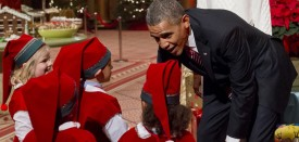 US President Barack Obama speaks with children dressed as elves, who are or were patients at Children's National Medical Center as they present donated gifts to the Obamas to give to children at the hospital, as they attend a taping of TNT's Christmas in Washington at the National Building Museum in Washington on December 15, 2013. The annual event, hosted by actor Hugh Jackman, features performances by the Backstreet Boys, Anna Kendrick, Sheryl Crow, Janelle Monae and Pat Monahan, and airs on the TNT television network on December 20.    AFP PHOTO / Saul LOEB        (Photo credit should read SAUL LOEB/AFP/Getty Images)
