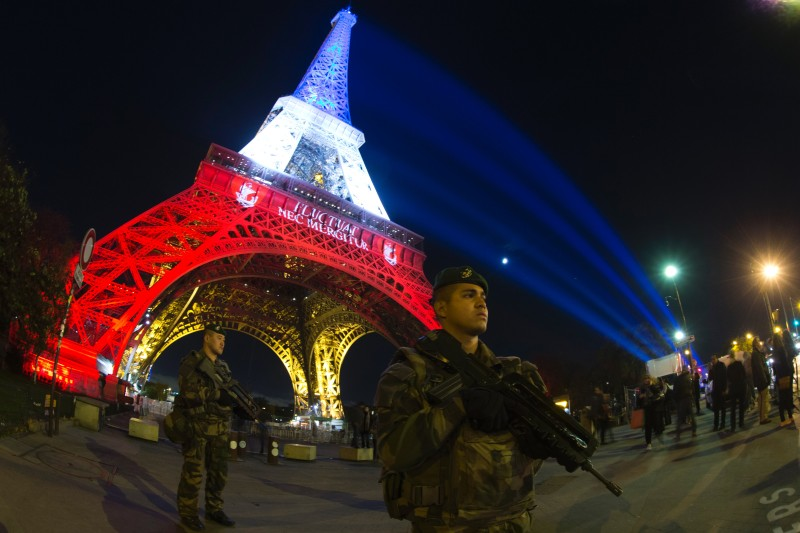 A French soldier enforcing the Vigipirate plan, France's national security alert system, is pictured on November 18, 2015 in Paris in front of the Eiffel Tower, which is illuminated with the colors of the French national flag in tribute to the victims of the November 13 Paris terror attacks in which some 129 people were killed.  / AFP / JOEL SAGET        (Photo credit should read JOEL SAGET/AFP/Getty Images)
