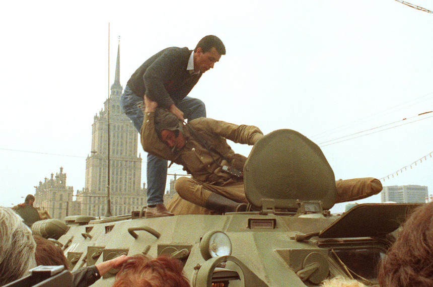 "MOSCOW, RUSSIA - AUGUST 19:  A pro-democracy demonstrator fights with a Soviet soldier on top of a tank parked in front of the Russian Federation building 19 August 1991 after a coup toppled Soviet President Mikhail Gorbachev. The coup was headed 19 August by the members of the self-styled ""committee for the state of emergency"" or the ""gang of eight"", including Soviet Vice President Gennady Yanayev and KGB chief Vladimir Kryuchkov. Thousands in Moscow, Leningrad and other cities answered the same day Russian Republic President Boris Yeltsin's call to raise barricades against tanks and troops. The collapse of the coup was signaled in the afternoon 21 August when the defence ministry ordered all troops to withdraw from Moscow.  (Photo credit should read DIMA TANIN/AFP/Getty Images)"