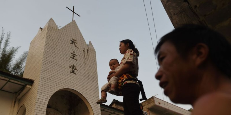 This photo taken on May 11, 2016 shows villagers outside the Catholic church in Changjing, in China's southern Guangxi region. The finishing touches are being put to a new museum in Dingan, the village where French missionary Auguste Chapdelaine died in 1856 and just a few kilometres from Changjing where he lived, celebrating the patriotism of his execution and condemning the spiritual opium of religion. / AFP / GREG BAKER / TO GO WITH China-culture-religion-Roman-Catholic-politics,FEATURE by Benjamin Carlson        (Photo credit should read GREG BAKER/AFP/Getty Images)