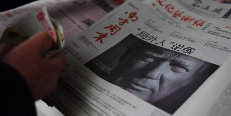 "A man buys a Chinese newspaper, with the headline that reads ""Outsider strikes back"", featuring Donald Trump on the front page in Beijing on November 10, 2016. The American public on November 9 voted for the Republican candidate Donald Trump to be the 45th President of the United States.  / AFP / GREG BAKER        (Photo credit should read GREG BAKER/AFP/Getty Images)"