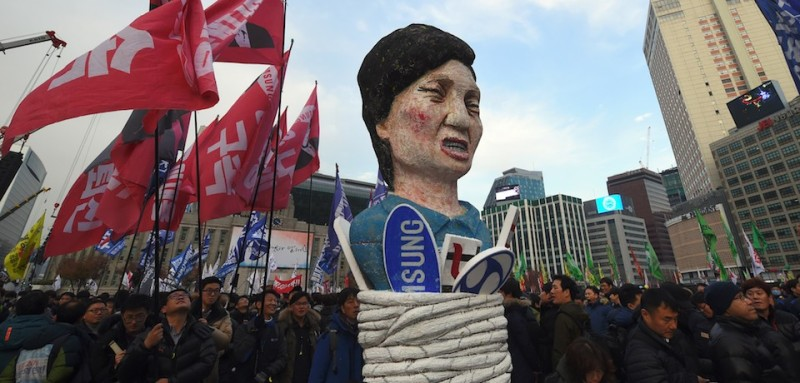 TOPSHOT - Protesters carry an effigy of South Korea's President Park Geun-Hye during an anti-government rally demanding the resignation of the president in central Seoul on November 30, 2016. An impeachment vote against South Korea's scandal-hit president will be postponed by at least a week, lawmakers said on November 30, after Park Geun-Hye announced she was willing to stand down early. / AFP / JUNG Yeon-Je        (Photo credit should read JUNG YEON-JE/AFP/Getty Images)