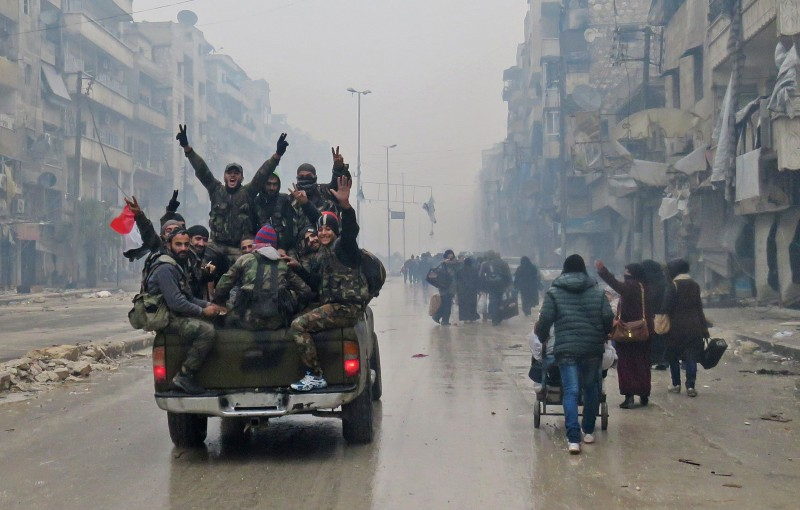 TOPSHOT - Syrian pro-regime fighters, gesture as they drive past residents fleeing violence in the restive Bustan al-Qasr neighbourhood, in Aleppo's Fardos neighbourhood on December 13, 2016, after regime troops retook the area from rebel fighters.  Syrian rebels withdrew from six more neighbourhoods in their one-time bastion of east Aleppo in the face of advancing government troops, the Syrian Observatory for Human Rights said. / AFP / STRINGER        (Photo credit should read STRINGER/AFP/Getty Images)