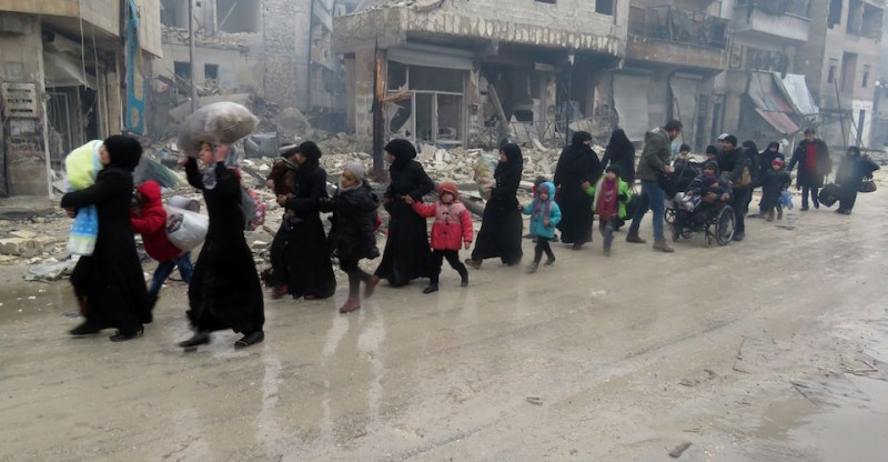 TOPSHOT - Syrian residents, fleeing violence in the restive Bustan al-Qasr neighbourhood, arrive in Aleppo's Fardos neighbourhood on December 13, 2016, after regime troops retook the area from rebel fighters.  Syrian rebels withdrew from six more neighbourhoods in their one-time bastion of east Aleppo in the face of advancing government troops, the Syrian Observatory for Human Rights said. / AFP / STRINGER        (Photo credit should read STRINGER/AFP/Getty Images)
