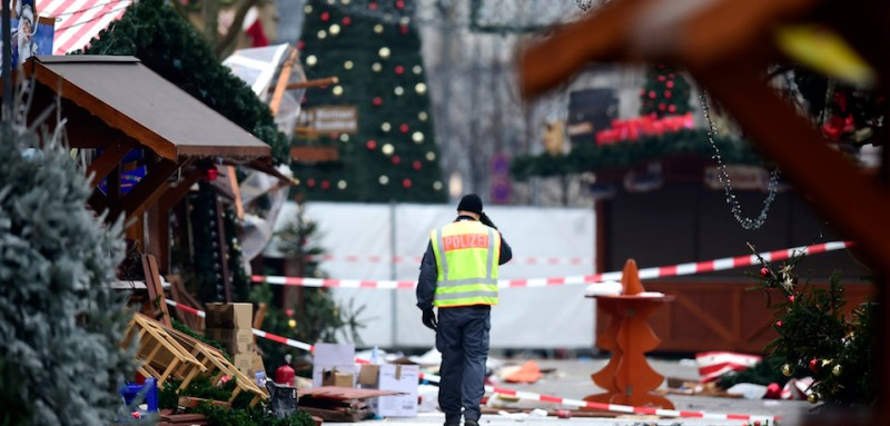 """TOPSHOT - A policeman walks at the Christmas market near the Kaiser-Wilhelm-Gedaechtniskirche (Kaiser Wilhelm Memorial Church), the day after a terror attack, in central Berlin, on December 20, 2016. German police said they were treating as """"a probable terrorist attack"""" the killing of 12 people when the speeding lorry cut a bloody swath through the packed Berlin Christmas market. / AFP / Tobias SCHWARZ        (Photo credit should read TOBIAS SCHWARZ/AFP/Getty Images)"""