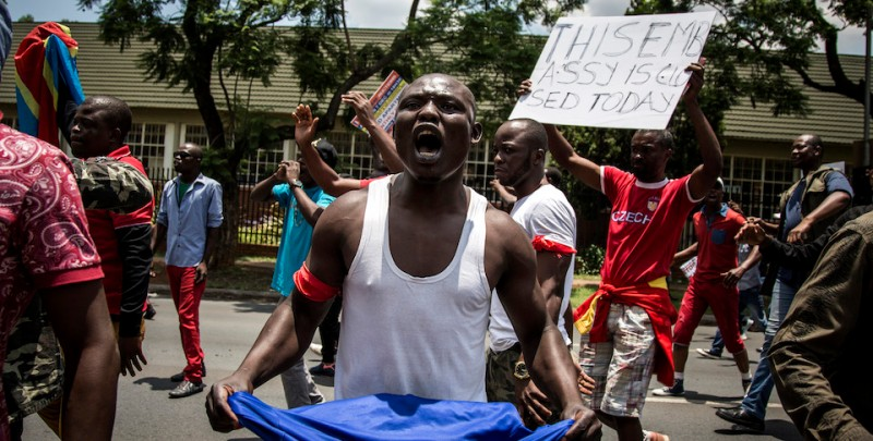 A Congolese protester holds a book of the DRC's constitution in defiance against the President of the Democratic Republic of the Congo, Joseph Kabila, at a protest demanding him to step down on December 20, 2016 in Pretoria. The United Nations voiced alarm over a wave of arrests in the Democratic Republic of Congo, where tensions were running high after President Joseph Kabila's term in office expired. Tuesday marked the end of the second and constitutionally-mandated final term for the 45-year-old, who inherited the presidency after the 2001 assassination of his father. But he is now refusing to leave the job that he began without much fanfare.   / AFP / John Wessels        (Photo credit should read JOHN WESSELS/AFP/Getty Images)