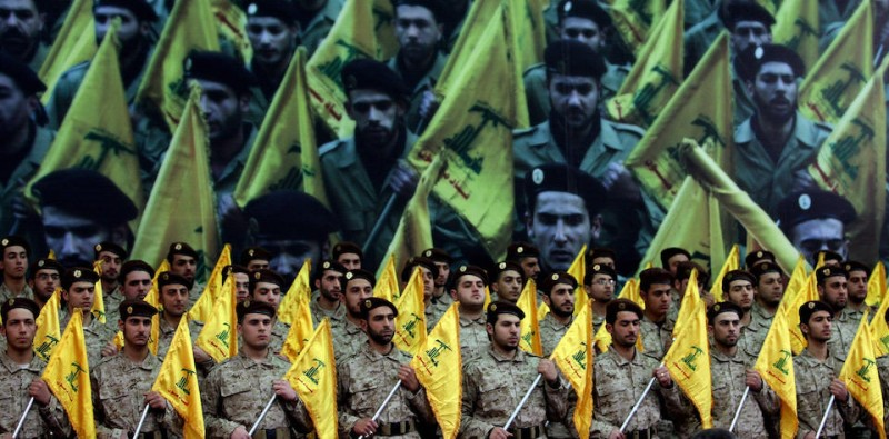 Shiite Muslims Hezbollah militants stand to attention as hundreds of people gather in a huge hall waiting to watch a televised speech by Hassan Nasrallah, the leader of the Shiite Muslim Lebanese Hezbollah militant group on February 22, 2008, in Beirut's southern suburb, ten days after the assassination of Hezbollah commander Imad Mughnieh in a bomb attack in Damascus. Nasrallah's televised speech marked the killing of Mughnieh and the 1992 assassination of its former leader Abbas Mussawi in an Israeli helicopter strike and assassinated Sheikh Ragheb Harb in 1984.  AFP PHOTO / JOSEPH BARRAK (Photo credit should read JOSEPH BARRAK/AFP/Getty Images)