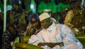 """Incumbent Gambian President Yahya Jammeh listens to one of his aides in Banjul on November 29, 2016, during the closing rally of the electoral campaign of the Alliance for Patriotic Reorientation and Construction (APRC).  More than 880,000 voters are expected to cast their ballots when the west African country goes to the polls on December 1, 2016. Jammeh has won four elections with his ruling Alliance for Patriotic Reorientation and Construction, following a 2002 constitutional amendment lifting term limits. Rights bodies and media watchdogs including Reporters Without Borders (RSF) accuse Jammeh of cultivating a """"pervasive climate of fear"""" and of crushing dissent against his regime, one cause of the mass exodus of Gambian youths to Europe. / AFP / MARCO LONGARI        (Photo credit should read MARCO LONGARI/AFP/Getty Images)"""