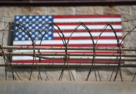 """GUANTANAMO BAY, CUBA - OCTOBER 22: (EDITORS NOTE: Image has been reviewed by the U.S. Military prior to transmission.)   Razor wire lines the fence of the """"Gitmo"""" maximum security detention center on October 22, 2016 at the U.S. Naval Station at Guantanamo Bay, Cuba. The U.S. military's Joint Task Force Guantanamo is still holding 60 detainees at the prison, down from a previous total of 780. On his second day in office in 2008 President Obama issued an executive order to close the prison, which has failed because of political opposition in the U.S.  (Photo by John Moore/Getty Images)"""