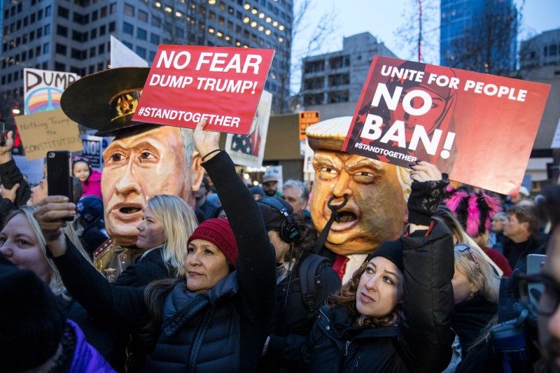 SEATTLE, WA - JANUARY 29: Protestors hold up signs in front of effigies of U.S. President Donald Trump and Russian President Vladimir Putin during in a demonstration on January 29, 2017 in Seattle, Washington, against Trump's executive order banning Muslims from certain countries. The rally was one of several in the area over the weekend. (Photo by Stephen Brashear/Getty Images)