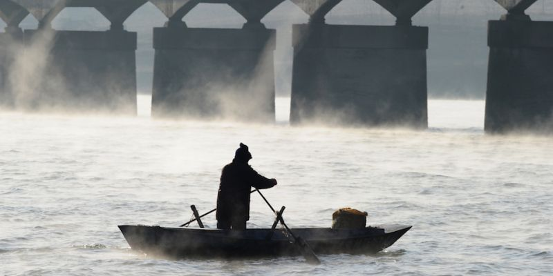 Steam rises off the freezing water as a Chinese man rows his boat along the Yalu River between China and North Korea some 70 kms north of the North Korean border town of Siniuju which lies across the river from Dandong in northeast China's Liaoning province on November 26, 2010. AFP PHOTO / Frederic J. BROWN (Photo credit should read FREDERIC J. BROWN/AFP/Getty Images)