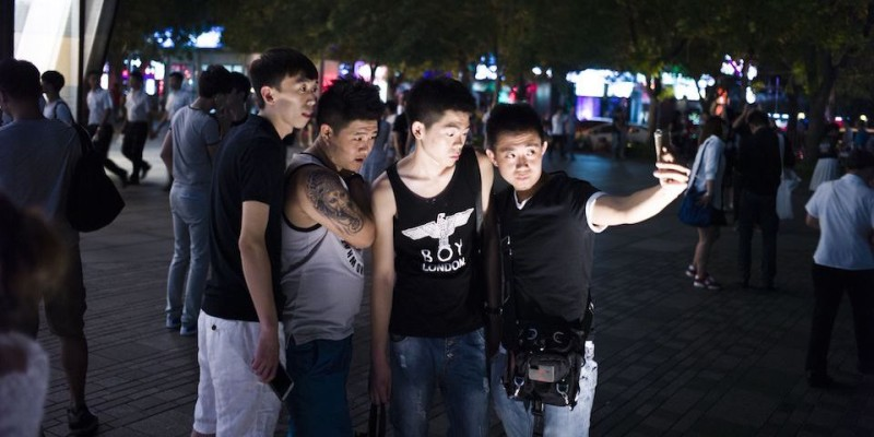 """In this picture taken on July 15, 2015, people gather in front of a Uniqlo clothes store in Beijing. Chinese Communist authorities have said the distribution of a sex tape purportedly shot in a fitting room in one of Beijing's trendiest shopping malls is """"against socialist core values"""", after the footage went viral.  AFP PHOTO / FRED DUFOUR        (Photo credit should read FRED DUFOUR/AFP/Getty Images)"""