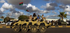 """Libyan troops loyal to Khalifa Haftar, a retired general and former chief of staff for Moamer Kadhafi, sit on an amoured personnel carrier (APC) during a demonstration calling on the international community to arm the Libyan army on August 14, 2015 in the eastern Libyan city of Benghazi. The Tobruk-based government (recognised by the international community) said in a statement that world powers were using """"double standards"""" by fighting IS in Syria and Iraq and """"turning a blind eye"""" to the presence of the jihadists in Libya.   AFP PHOTO / ABDULLAH DOMA        (Photo credit should read ABDULLAH DOMA/AFP/Getty Images)"""