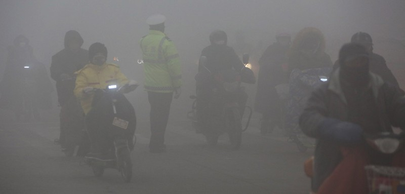 ZAOZHUANG, CHINA - JANUARY 03:  A traffic policeman regulates traffic in heavy smog on January 3, 2017 in Zaozhuang, China. Anhui issues an orange alert of fog at 11 a.m. on Tuesday.  (Photo by VCG/VCG via Getty Images)