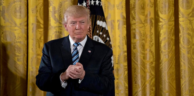 """WASHINGTON, DC - JANUARY 22: U.S. President Donald Trump listens during a swearing in ceremony of White House senior staff in the East Room of the White House on January 22, 2017 in Washington, DC. Trump today mocked protesters who gathered for large demonstrations across the U.S. and the world on Saturday to signal discontent with his leadership, but later offered a more conciliatory tone, saying he recognized such marches as a """"hallmark of our democracy."""" (Photo by Andrew Harrer-Pool/Getty Images)"""