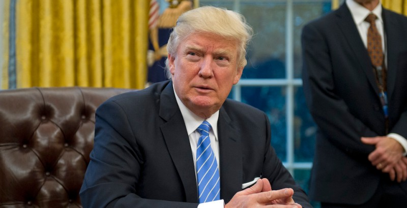 "WASHINGTON, DC - JANUARY 23:  (AFP OUT) U.S. President Donald Trump prepares to sign three Executive Orders in the Oval Office of the White House in Washington, DC on Monday, January 23, 2017.  These concerned the withdrawal of the United States from the Trans-Pacific Partnership (TPP), a US Government hiring freeze for all departments but the military, and ""Mexico City"" which bans federal funding of abortions overseas. (Photo by Ron Sachs - Pool/Getty Images)"
