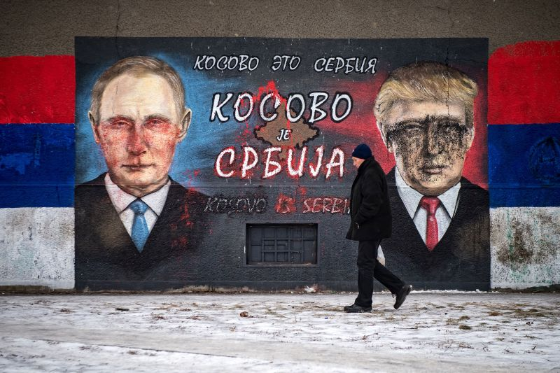 "A man walks past a mural, vandalized with paint, depicting Russian President Vladimir Putin (L) and US President Donald Trump and bearing the Cyrillic letters reading ""Kosovo is Serbia"", in Belgrade on January 25, 2017.   / AFP / ANDREJ ISAKOVIC / RESTRICTED TO EDITORIAL USE - TO ILLUSTRATE THE EVENT AS SPECIFIED IN THE CAPTION        (Photo credit should read ANDREJ ISAKOVIC/AFP/Getty Images)"
