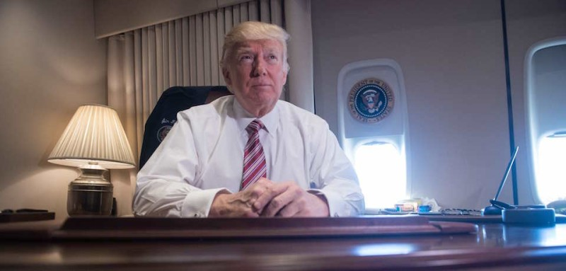 US President Donald Trump poses in his office aboard Air Force One at Andrews Air Force Base in Maryland after he returned from Philadelphia on January 26, 2017. / AFP / NICHOLAS KAMM        (Photo credit should read NICHOLAS KAMM/AFP/Getty Images)