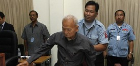 A security officer assists former Khmer Rouge leader Nuon Chea at the tribunal in the Court of Cambodia (ECCC) in Phnom Penh on February 4, 2008.  Nuon Chea sought to delay his first public hearing before Cambodia's genocide tribunal, saying that he needed his foreign lawyer to appeal his detention by the court. AFP PHOTO / POOL/ CHOR SOKOUNTHEA (Photo credit should read CHOR SOKOUNTHEA/AFP/Getty Images)
