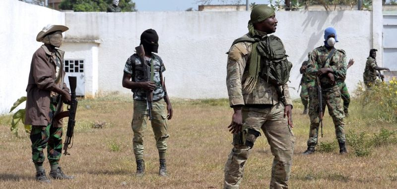 Former war chief of Bouake, lieutenant-colonel Issiaka Ouattara (R), also known as Wattao, flanked by mutineer soldiers, arrives at the deputy prefect's residence in Bouake for talks with the deputy prefect and Defence Minister on January 7, 2017 one day after soldiers rose up and seized control of Ivory Coast's second city.  Soldiers seized control of Bouake on January 6 in a protest over pay, firing rocket launchers in the streets and terrifying residents, as the government called for calm. The protests in Bouake spread to the central towns of Daloa and Daoukro as well as Korhogo in the north, as angry troops took to the streets demanding salary hikes.   / AFP / SIA KAMBOU        (Photo credit should read SIA KAMBOU/AFP/Getty Images)