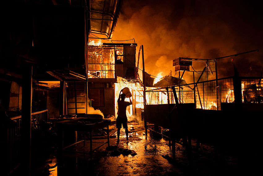 TOPSHOT - A resident pours water on a fire as it destroys hundreds of  houses at an informal settlers community in Delpan, Tondo, Manila on February 7, 2017. / AFP / NOEL CELIS / The erroneous mention[s] appearing in the metadata of this photo by NOEL CELIS has been modified in AFP systems in the following manner: [February] instead of [January]. Please immediately remove the erroneous mention[s] from all your online services and delete it (them) from your servers. If you have been authorized by AFP to distribute it (them) to third parties, please ensure that the same actions are carried out by them. Failure to promptly comply with these instructions will entail liability on your part for any continued or post notification usage. Therefore we thank you very much for all your attention and prompt action. We are sorry for the inconvenience this notification may cause and remain at your disposal for any further information you may require.        (Photo credit should read NOEL CELIS/AFP/Getty Images)