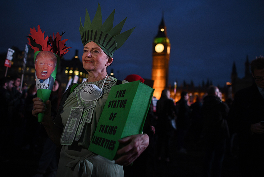 TOPSHOT - A protestor poses for a picture at an anti-Trump protest near the Houses of Parliament in London on February 20, 2017, as parliament debates whether or not to allow Donald Trump a state visit. / AFP / Justin TALLIS        (Photo credit should read JUSTIN TALLIS/AFP/Getty Images)