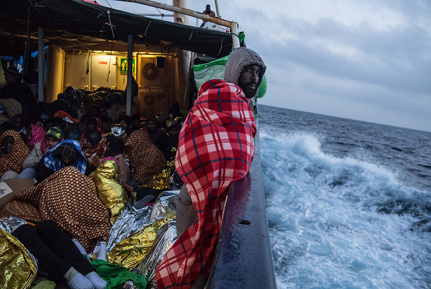 AT SEA, AT SEA - FEBRUARY 19:  Refugees and migrants are seen on deck of the Spanish NGO Proactiva Open Arms rescue vessel Golfo Azzurro sailing towards the Italian port of Pozzallo after being rescued off Libyan coast north of Sabratha, Libya on February 19, 2017 at Sea. 466 migrants were rescued in high seas last Friday by the Italian Coast Guard and the Spanish NGO Proactiva Open Arms rescue vessel Golfo Azzurro. Proactiva Open Arms are a Spanish charity based out of Malta who provide search and rescue assistance to refugees and migrants in distress at sea. They patrol the SAR and Rescue Zone off the coast of Libya running rescue missions for the hundreds of migrants who continue to make perilous journey across the Mediterranean in hope of reaching the European mainland.  (Photo by David Ramos/Getty Images)