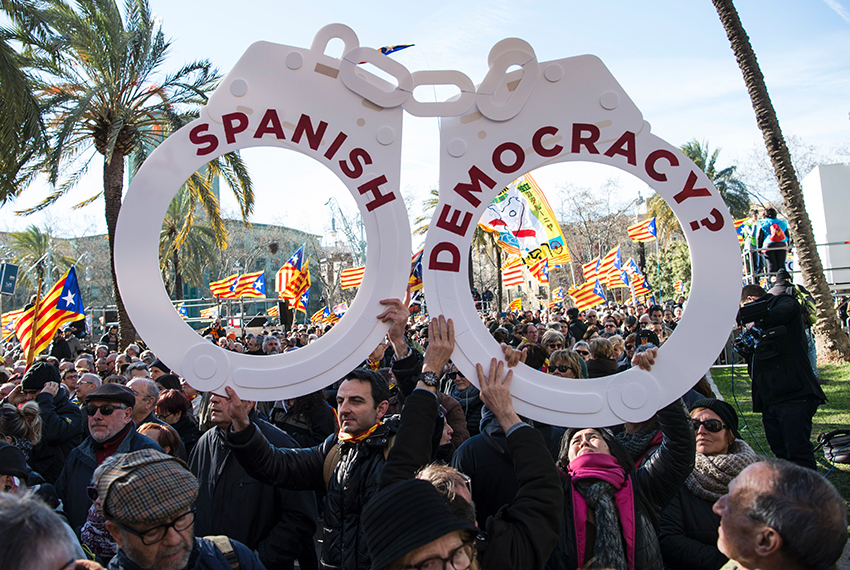 "TOPSHOT - People hold big handcuffs reading ""Spanish democracy"" outside the TSJC (Superior Court of Catalonia) in Barcelona on February 6, 2017 during the first day of the trial of former President of the Catalan Government and leader of Partit Democrata Europeu Catala (Catalan European Democratic Party) PDECAT Artur Mas in Barcelona on February 6, 2017. Mas is charged with civil disobedience and misuse of public funds for holding a non-binding ballot on November 9, 2014 (9N) in which Catalans were asked to vote on whether their region should remain part of Spain. / AFP / Josep Lago        (Photo credit should read JOSEP LAGO/AFP/Getty Images)"