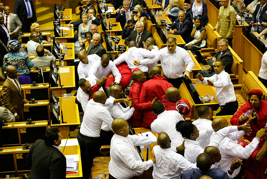 TOPSHOT - Security officials force out South African opposition party Economic Freedom Fighters (EFF) members during South African President's speech for the 2017's State Of the Nation Address(SONA), on February 9, 2017, in Cape Town. A violent brawl broke out in South Africa's parliament on February 9, 2017 as guards exchanged punches with opposition lawmakers who had shouted down President Jacob Zuma as he tried to deliver his state of the nation address. In chaotic scenes, about 30 guards dressed in white shirts forcibly ejected about 25 members from the radical leftist Economic Freedom Fighters (EFF) party who had prevented the president from speaking for about an hour. / AFP / POOL / SUMAYA HISHAM        (Photo credit should read SUMAYA HISHAM/AFP/Getty Images)