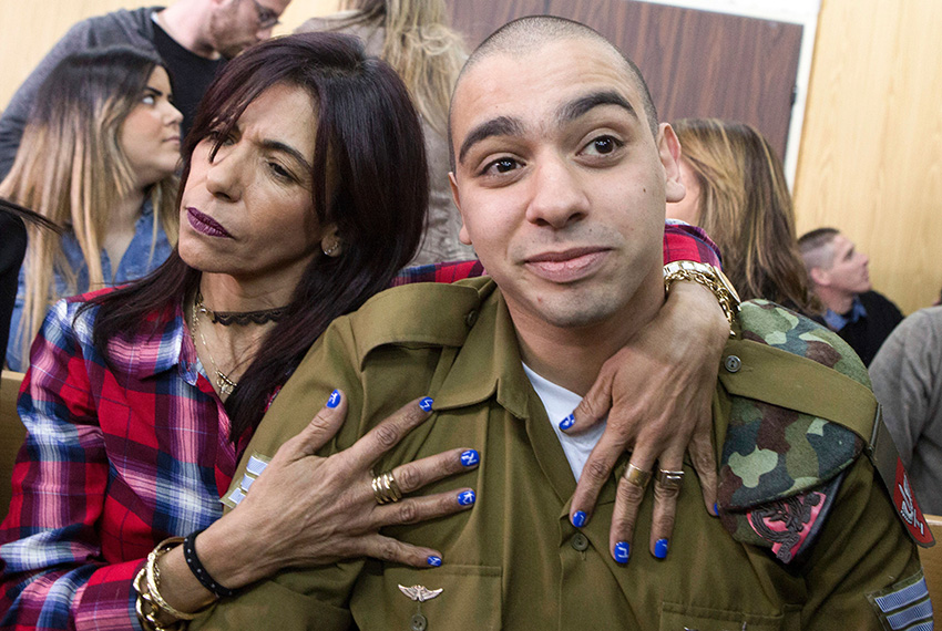 TOPSHOT - Israeli soldier Elor Azaria (R), who shot dead a wounded Palestinian assailant in March 2016, is embraced by his mother Oshra (L) at the start of his sentencing hearing in a military court in Tel Aviv on February 21, 2017.  An Israeli military court will sentence a soldier convicted of the manslaughter of a Palestinian attacker in a case which has stoked passions, debate and protest. / AFP / POOL / JIM HOLLANDER        (Photo credit should read JIM HOLLANDER/AFP/Getty Images)