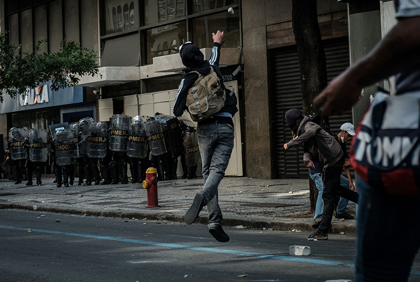 Men throw stones at Military Police during a protest against the privatization of  Rio de Janeiro state water and sewerage utility (CEDAE) in Rio de Janeiro, Brazil, on February 9, 2017. / AFP / Yasuyoshi Chiba        (Photo credit should read YASUYOSHI CHIBA/AFP/Getty Images)