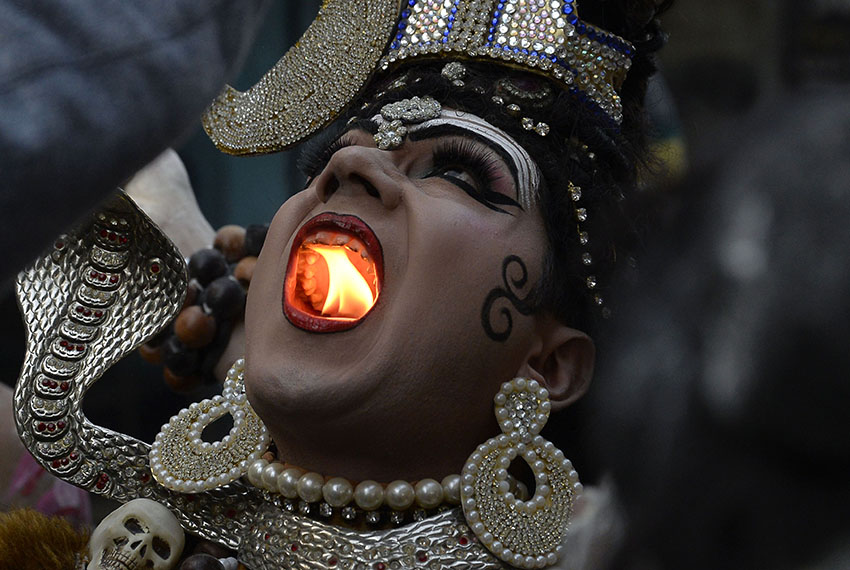TOPSHOT - An Indian Hindu man dressed as Lord Shiva holds a lit candle in his mouth as he takes part in a religious procession ahead of the Maha Shivratri Festival in Jalandhar on February 22, 2017.  Hindus mark the Maha Shivratri festival by offering special prayers and fasting to worship Lord Shiva, the lord of destruction. / AFP / SHAMMI MEHRA        (Photo credit should read SHAMMI MEHRA/AFP/Getty Images)