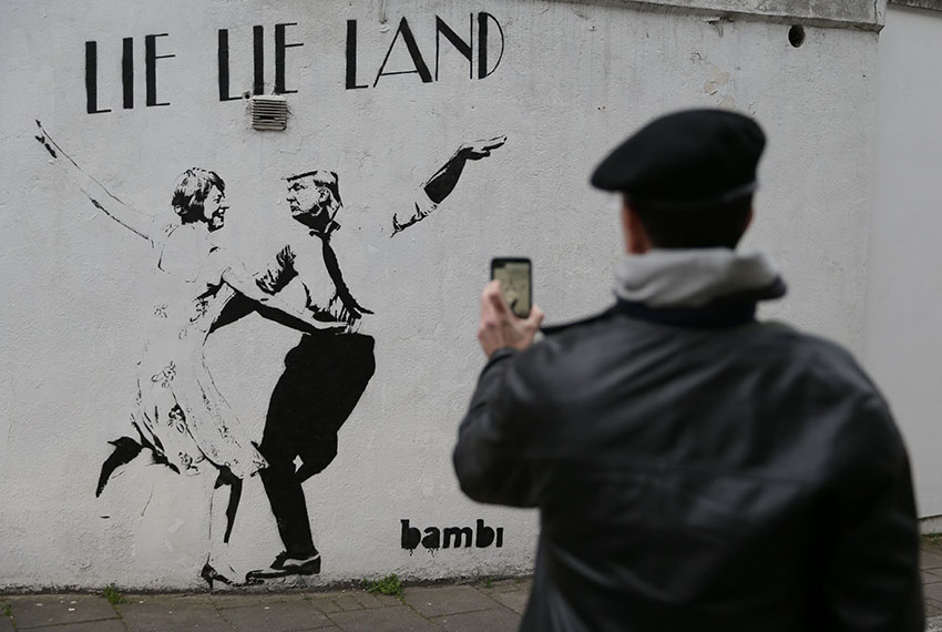 TOPSHOT - A man takes a picture of a mural by English street artist Bambi depicting British Prime Minister Theresa May dancing with US President Donald Trump in London on February 22, 2017.  / AFP / Daniel LEAL-OLIVAS / RESTRICTED TO EDITORIAL USE - MANDATORY MENTION OF THE ARTIST UPON PUBLICATION - TO ILLUSTRATE THE EVENT AS SPECIFIED IN THE CAPTION        (Photo credit should read DANIEL LEAL-OLIVAS/AFP/Getty Images)